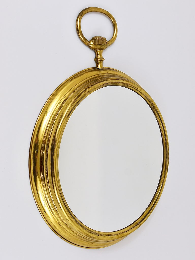 A huge 23 inches high round midcentury brass wall mirror in the shape of a pocket watch. Made in Italy in the 1950s. In the style of Piero Fornasetti. In very good original condition, with the original mirror glass and nice patina on the brass.