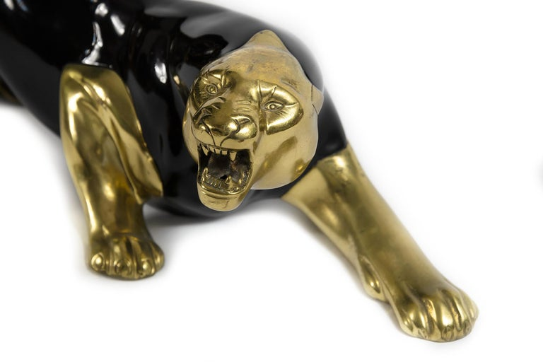 Midcentury panther sculpture is designed in bronze and decorated with black enamel. It is very solid and heavy.