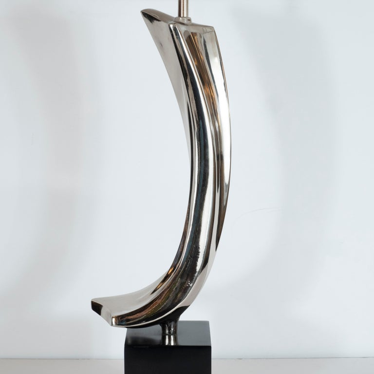 This sculptural and dynamic Mid-Century Modern lamp was designed by the illustrious Maurizio Tempestini for the Laurel Lamp Company in the United States, circa 1960. Forged in lustrous chrome- offering the appearance of quick silver- it features