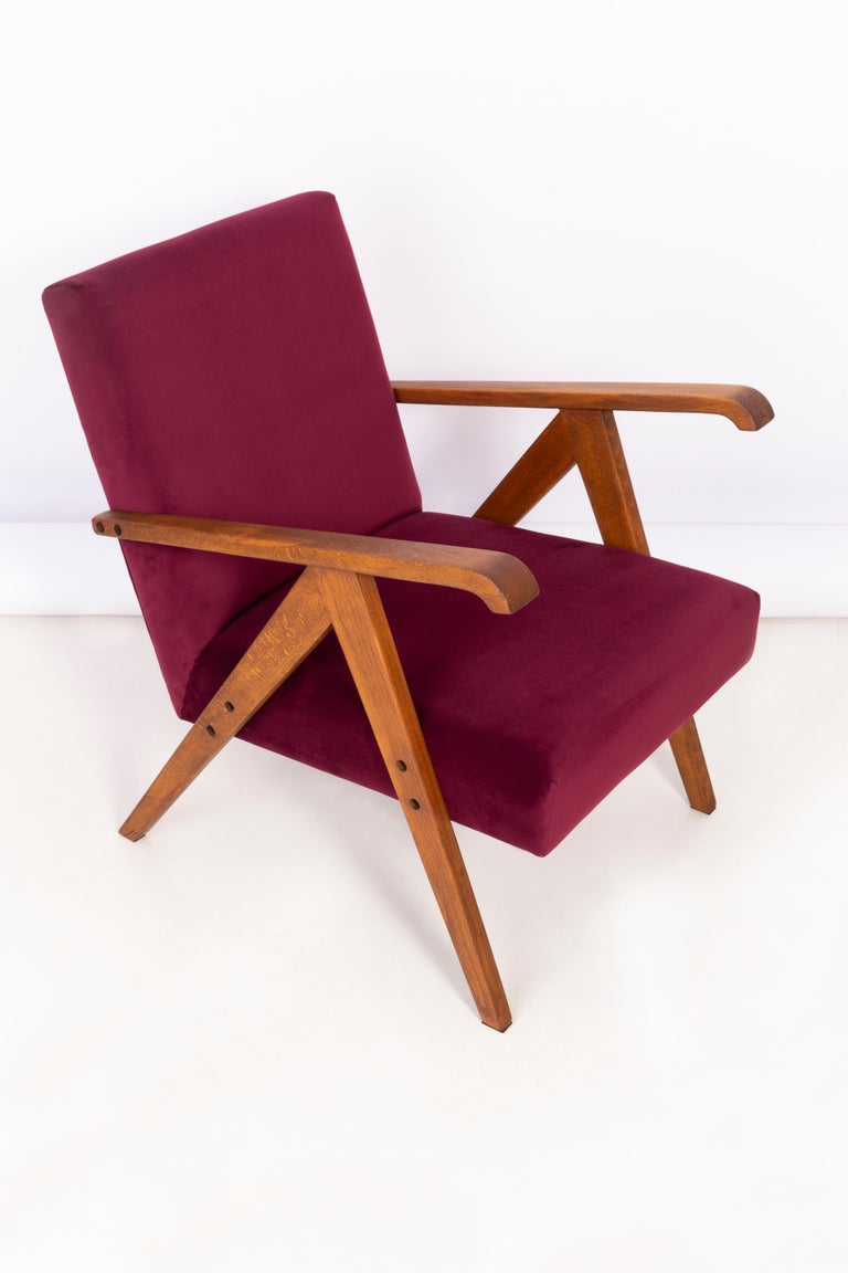 A beautiful, restored armchair designed by Henryk Lis. Furniture after full carpentry and upholstery renovation. The fabric, which is covered with a backrest and a seat, is a high-quality burgundy velvet upholstery (color 2932). The armchair will be