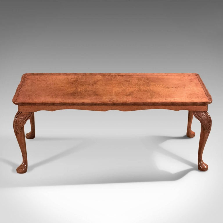 This is a good quality midcentury coffee table in the high Victorian taste.  An attractive narrow coffee table presented in excellent condition Displaying quality burr walnut top, classically 'bookmatched' Raised on pad feet to elegant cabriole