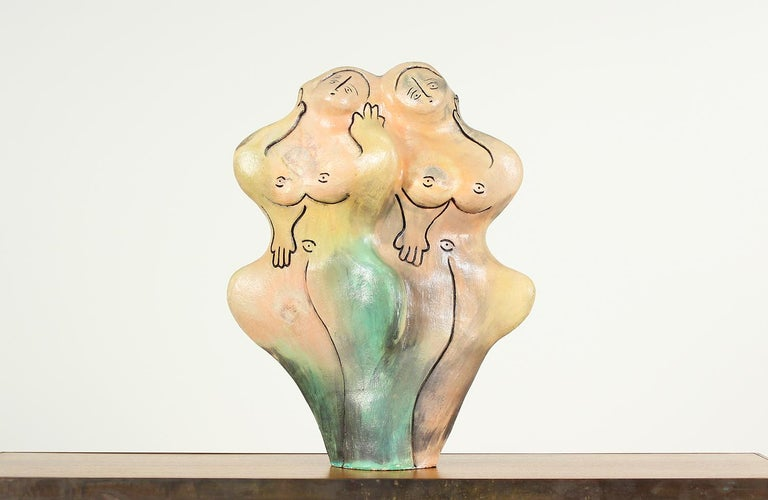 Large free-form female sculpture designed in the United States circa 1960. This interesting art piece features two entwined nude women in earth-toned ceramic. Black lines trace their faces, hands, and bodies. Their facial expressions and body