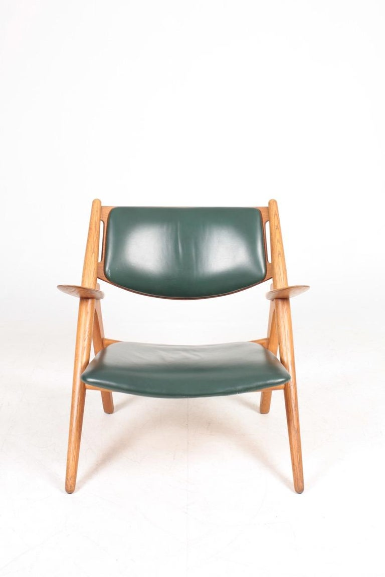 Lounge chair in oak and patinated leather. Designed by Hans J. Wegner M.A.A for Carl Hansen furniture. Great original condition. Made in Denmark.
