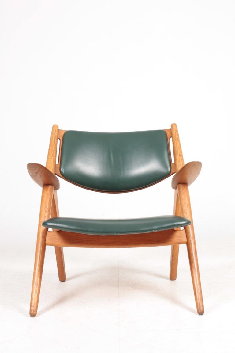 Scandinavian Modern Midcentury CH-28 Lounge Chair in Oak and Patinated Leather by Hans Wegner, 1960s For Sale