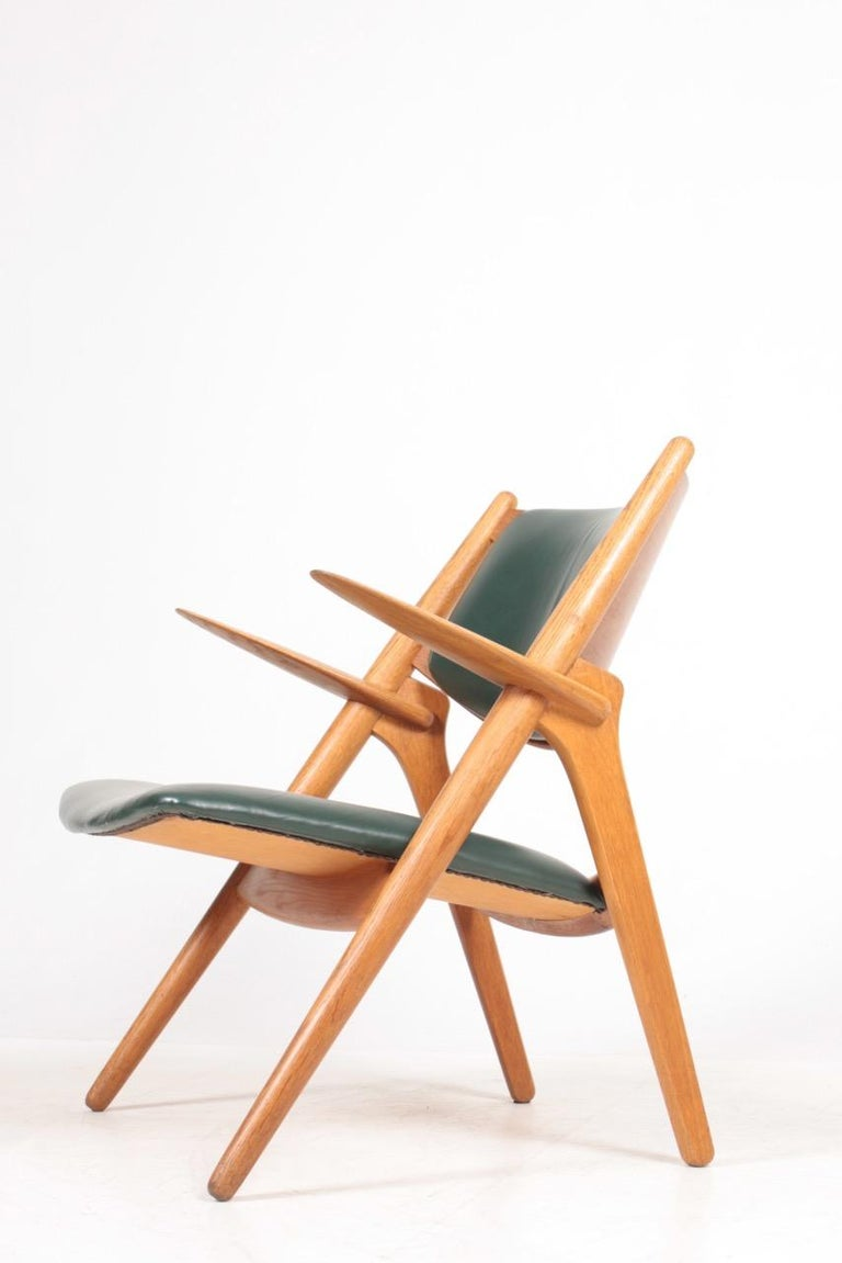 Mid-20th Century Midcentury CH-28 Lounge Chair in Oak and Patinated Leather by Hans Wegner, 1960s For Sale
