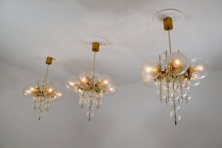 This set of three brass chandeliers was produced in Europe in the 1970s. A spirited and chic design set of three chandeliers with brass fixture and art-glass. The chandelier with brass frame consist of six lights, formed in a circle, with glass