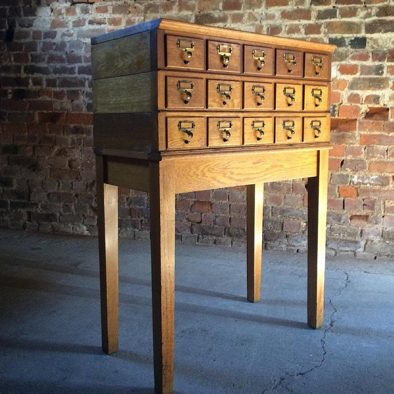 A magnificent mid-20th century haberdashery industrial oak stacking office chest cabinet, having a bank of 15 drawers each with brass index card holder, raised on a base with square section supports, the eleven drawer sections each stack on top of