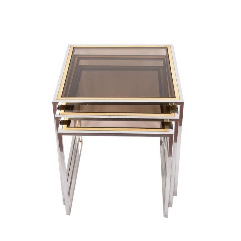 Wonderful set of three nesting tables in chromed metal, brass and smoked glass.  These Mid-Century Modern amazing tables were produced in Italy during the 1970s.   This set, both elegant and functional, is perfect for a midcentury living