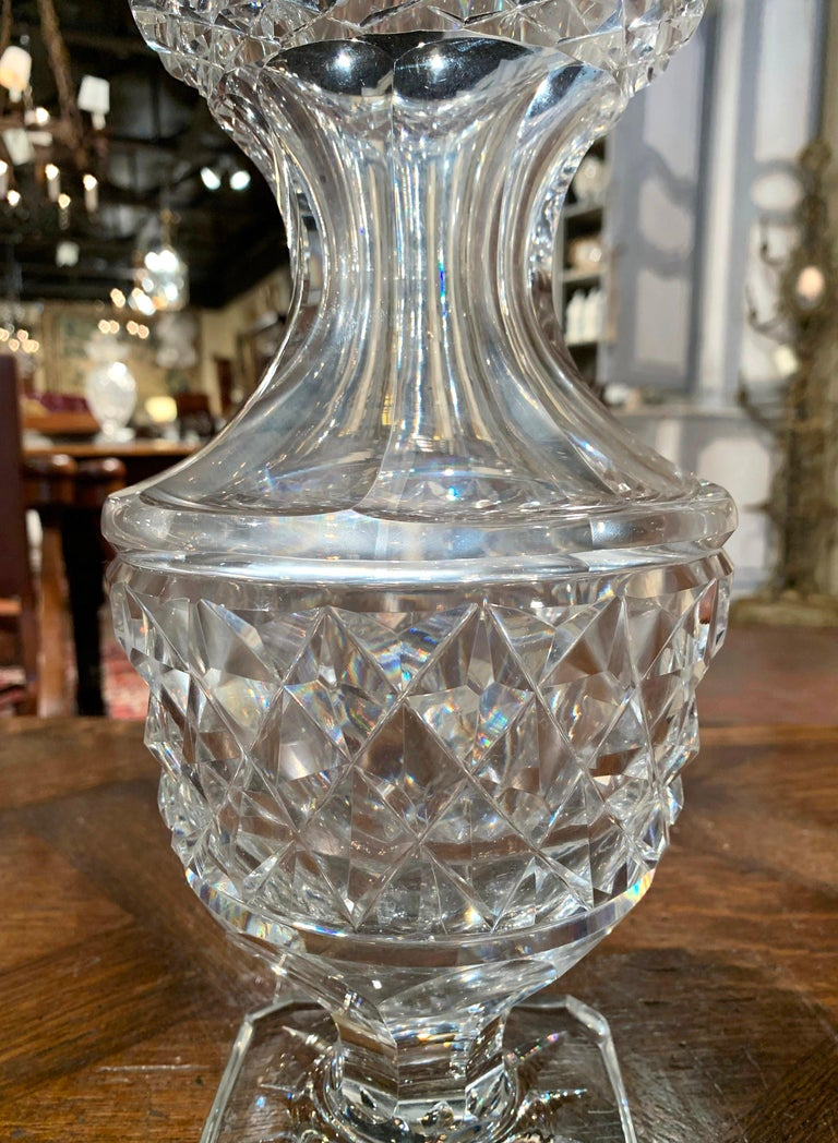 Decorate a console table or buffet with this elegant glass vase. Crafted in France circa 1970, the luxurious cut glass vessel stands on a square base, is shaped as a neoclassical urn with a wide mouth at the top, and is decorated throughout with