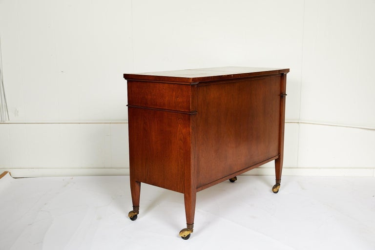 This 20th century vintage sideboard features a walnut finish on all sides, convertible black formica top, and casters for versatility and easy service. The case holds one wide drawer with brass ring pulls above two Regency style paneled doors with