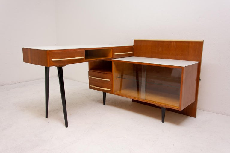 Midcentury corner writing desk with a small bookcase. It was produced by UP Závody and made in the 1960s in the former Czechoslovakia. It features probably an ashwood or elm wood veneer and white opaxite glass on the top.  Very simple design,