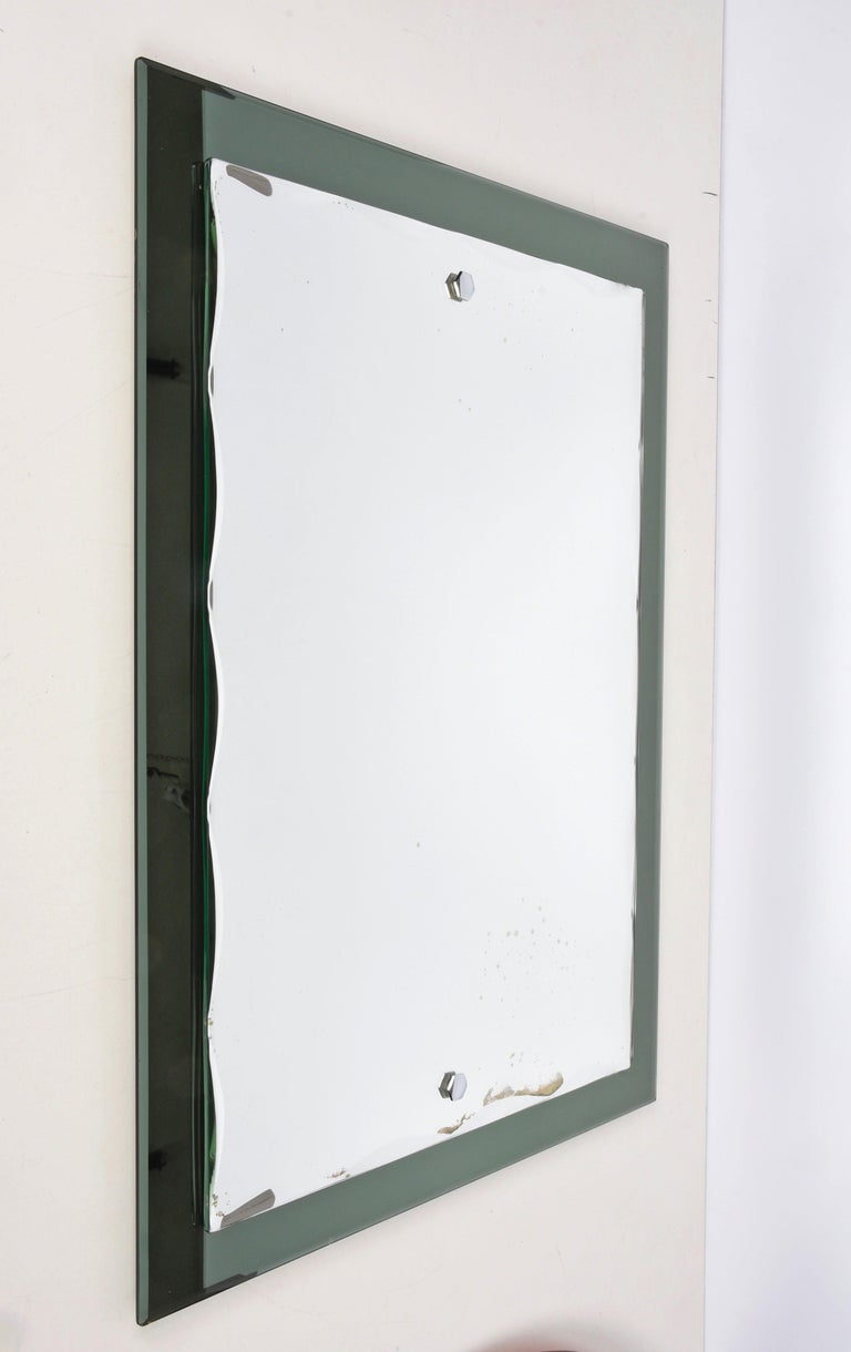 Beautiful midcentury mirror with olive green glass frame and carved rectangular mirror. This Italian mirror was designed in the style of Cristal Arte and was made in Italy during the 1960s.  This piece is an example of excellent Italian