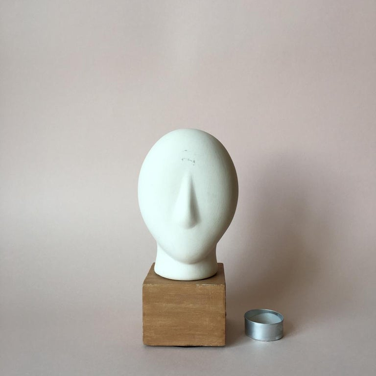 Minimalist head sculpture made of matte clay on a faux wood base. The head color is off-white and it is very pleasant to touch.