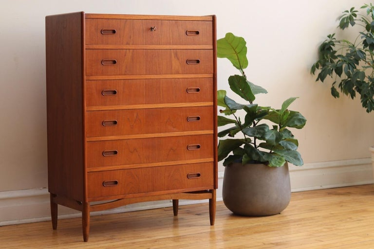 Mid-Century Modern Danish teak wood chest of drawers. Just imported from Copenhagen! Six drawers with two handles on each drawer. Top drawer locks and includes a vintage key. Continuous woodgrain down the drawer fronts. Beautifully refinished