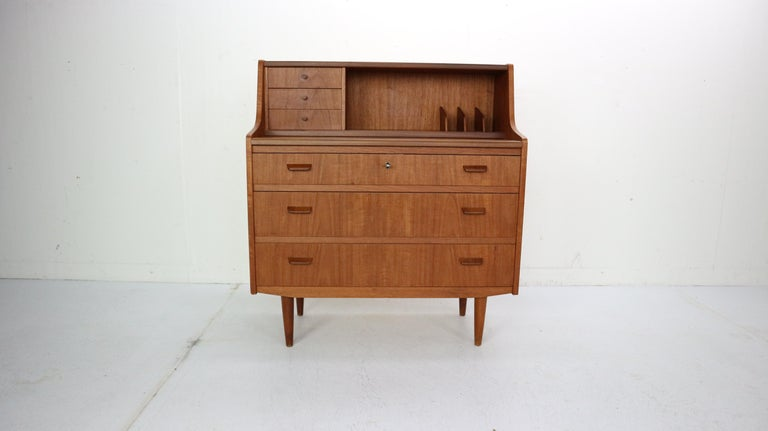 This midcentury Danish modern teak secretary desk was made in Denmark, circa 1960. The Classic Scandinavian Modern design has clean Minimalist lines and elegant curves. The upper cabinet features three small top drawers, storage space and a pull-out