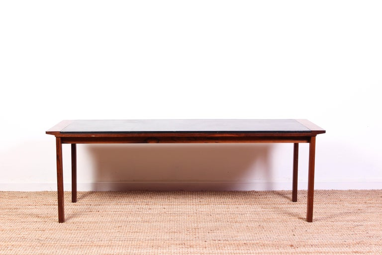 A midcentury Danish coffee table attributed to Ejvind A Johansson. The coffee table is made out of at rosewood frame and a black leather tabletop. It is in very good vintage condition with some signs of usage on the tabletop consistent with age and