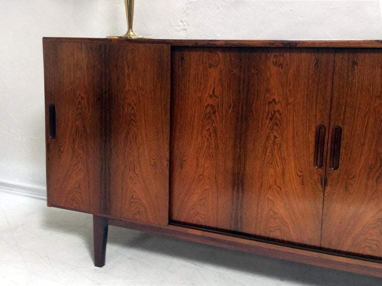 A superb Danish rosewood highboard in the style of Gunni Omann. The left hand door slides to reveal five green baise lined drawers, the central and right hand compartment contain adjustable shelves. Super build quality, lovely veneers and in