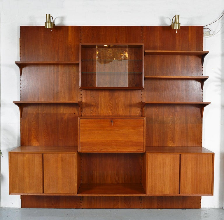 A highly versatile and functional three-bay teak Cado wall system by Danish designer Poul Cadovius. Comprising of three backboards, two cupboards, drop-down bar, glass fronted cabinet, six shelves and brackets - completed by a pair of adjustable
