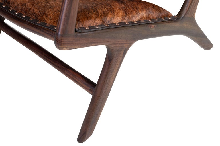 1950s design and Scandinavian style for this lounge armchair, at the manner of Hans J. Wegner for Carl Hansen, composed of an original and airy teak wooden structure, a seat and backrest dressed with cow skin.