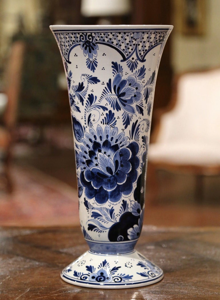 Decorate a mantel (fireplace) or buffet with this tall, ceramic vase from Holland; sculpted circa 1960, the traditional antique vase features a tapered form with a long neck and a wide mouth. The ceramic vase is hand painted with bird and floral
