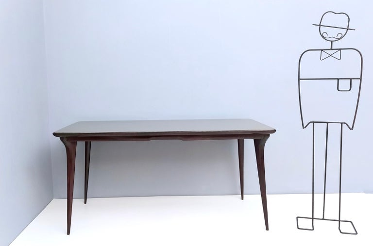 1950s. This table is made in ebonized beech and features a taupe back-painted glass top.  It is a vintage item, therefore it might show slight traces of use, but it can be considered as is in excellent original condition and ready to become a piece