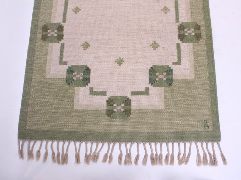 A midcentury flat-weave carpet designed by Swedish designer Anna-Johanna Ångström. The carpet green base and patterns of different green shades and an off-white/grey. Very good vintage condition with original lashes and minor signs of usage.