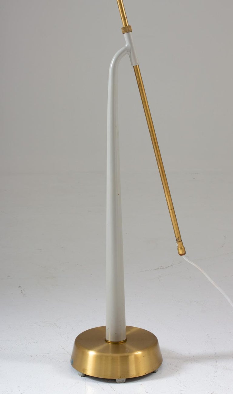Lovely floor lamp model 541 in brass and metal by Hans Bergström for Swedish manufacturer Ateljé Lyktan.  The lamp consists of a brass and grey metal base, supporting a brass rod that is adjustable in height.  Maximum height is 165cm