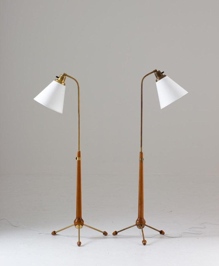Lovely tripod floor lamps in brass and stained beech by Hans Bergström for Swedish manufacturer Ateljé Lyktan. The height of the lamps are adjustable.