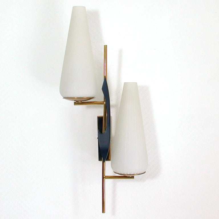 This large awesome French wall light was produced by Maison Arlus in the 1950s. It is made of brass black lacquered iron and has got two opaline glass lamp shades.  The light requires two B22 French bayonet bulbs. It is in very good condition and