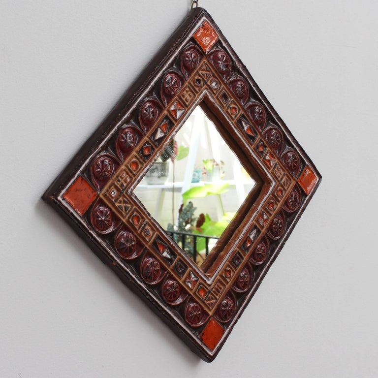 Midcentury French ceramic decorative mirror attributed to Atelier Les Cyclades, Anduze, France, circa 1960s-1970s. A ceramic frame with inset enamel decorative shapes form this colorful square mirror. The glass centre piece is enclosed by