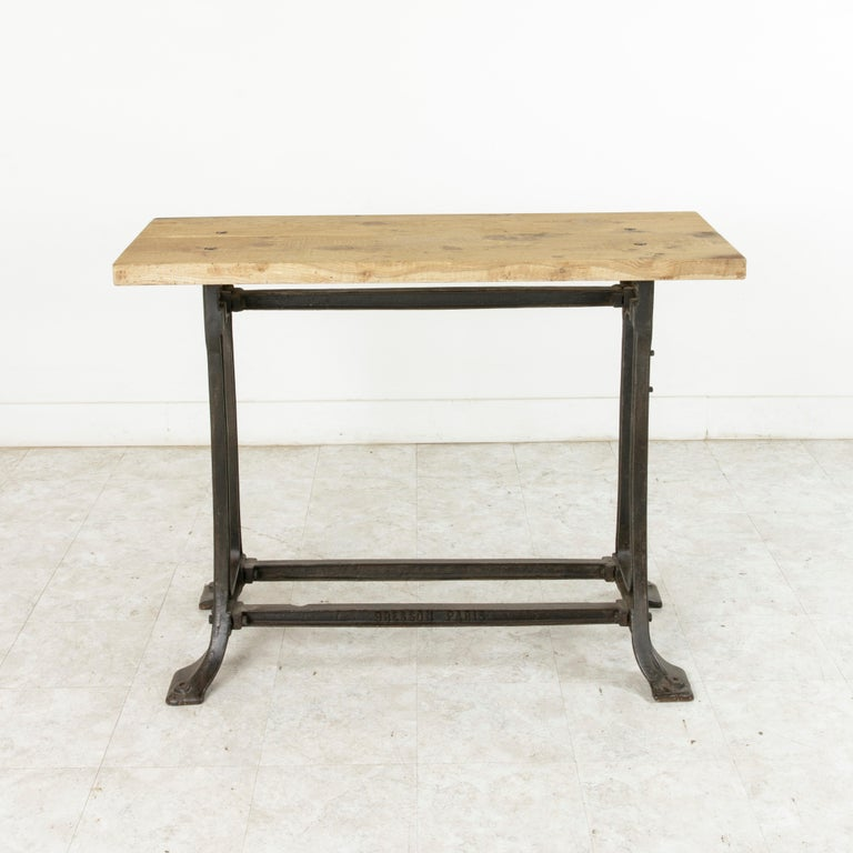 This early 20th century French Industrial console table or work table stands at 36.5 inches in height and features a two inch thick oak top constructed of two planks of wood joined by a spline that runs the length of the tabletop. The top rests on a