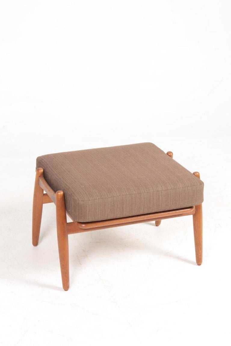 Ottoman in oak with fabric seat, designed by Maa. Hans J. Wegner and made by GETAMA Denmark. Great original condition.