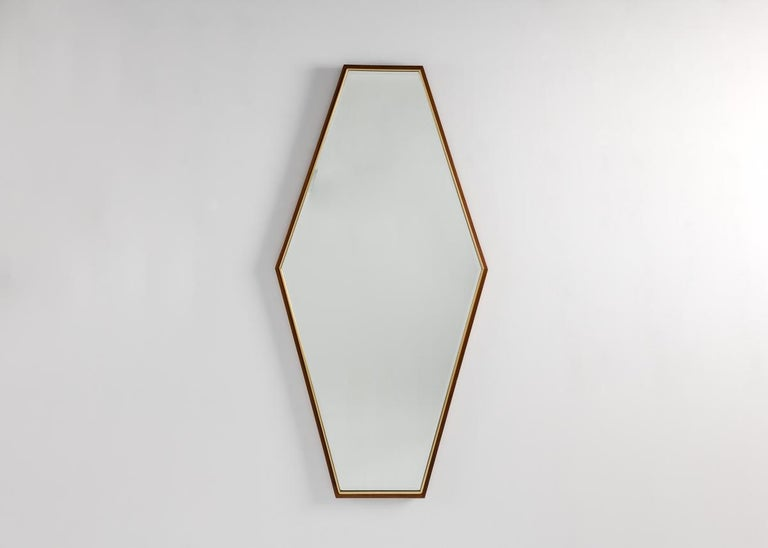 A pair of large midcentury mirrors in vertical hexagonal shapes framed in thin borders of painted wood.