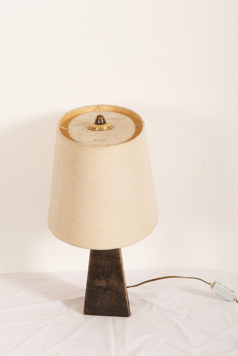 Brass base covered with goatskin fitted with two E27 sockets. Made in the early 1960 in Italy by Aldo Tura.  Age and signs of use. Screens with minor damage or stains. Vintage original condition.