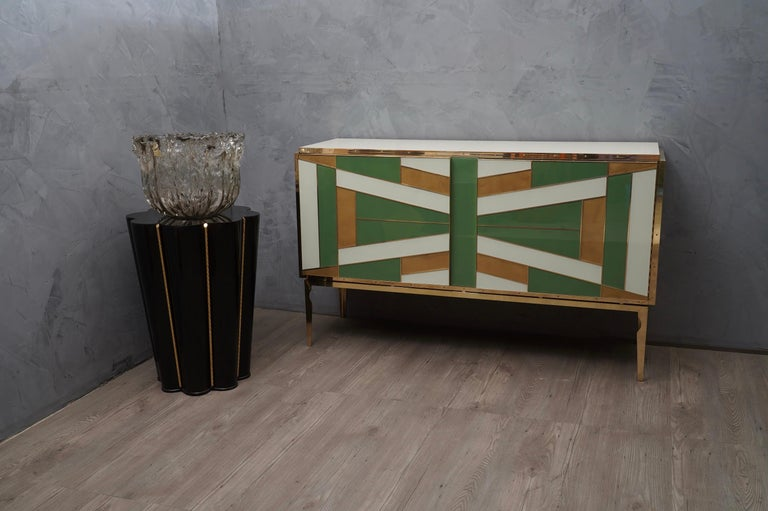 Very special multi-color glass sideboard beautifully matched with green gold and light ivory.  The sideboards have a wooden structure, externally they have been plated with glass of different colors and then edged with polished brass finishes. Brass
