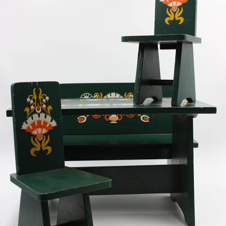 Hand-painted floral motif green dolls furniture from the 1940s in the style of Dora Kuhn. Complete dining room set with a bench, two chair, table an China cabinet. Chest of drawers and a wardrobe.