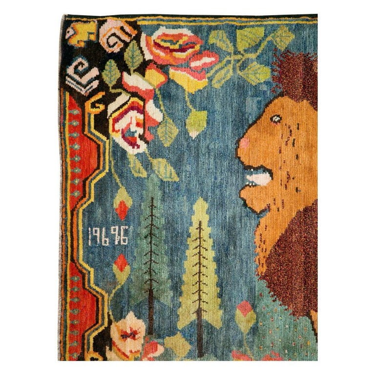 A vintage Caucasian Karabagh pictorial accent rug handmade during the mid-20th century. A male lion looks left over a cerulean blue and seafoam green polka dot field that encompasses two large cypress trees and large scale European floral