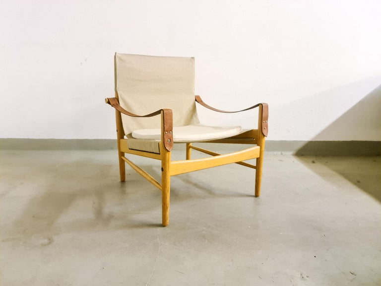 Beautiful safari chair designed by Hans Olsen for Viska Möbler in Kinna, Sweden. This chairs are made of oak with a new canvas Swedish quality linen upholstery.  Good vintage condition oak frame with, the leather armrests with nice patina.