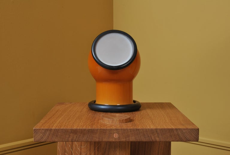 A wonderful midcentury Holmegaard glass Epoke lamp. Designed by Michael Bang for Holmegaard, Denmark, 1972. A playful and characterful design with a slightly nautical nature. Orange main case with white cap. Heavy glass with rubber