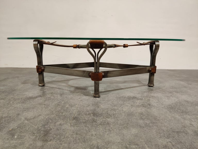 Beautiful coffee table made from iron and leather with an oval clear glass top.   Great design, which can fit in in the popular brutalist design style nowadays.  1960s - France  Good condition  Dimensions: Height 34cm/13.38