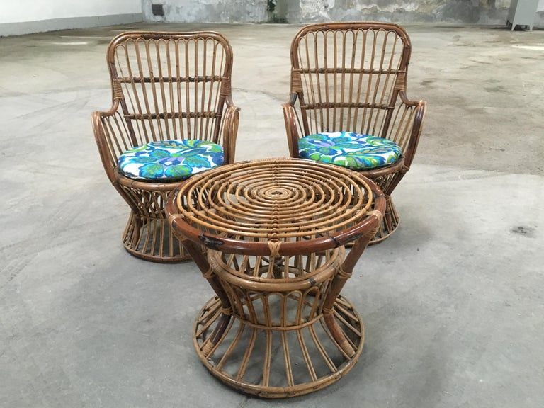 Italian bamboo and rattan living room set from 1950s composed by a pair of armchairs with vintage floral fabric cushions and a side table
