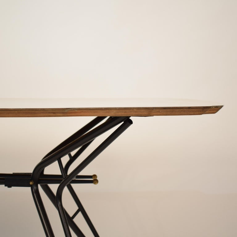 This extraordinary midcentury Italian dining table is attributed to Ico Parisi and Paolo di Poli. It is made out of black lacquered metal, Formica and brass. It has got a fantastic shape and the base is beautifully architectural. It is in beautiful