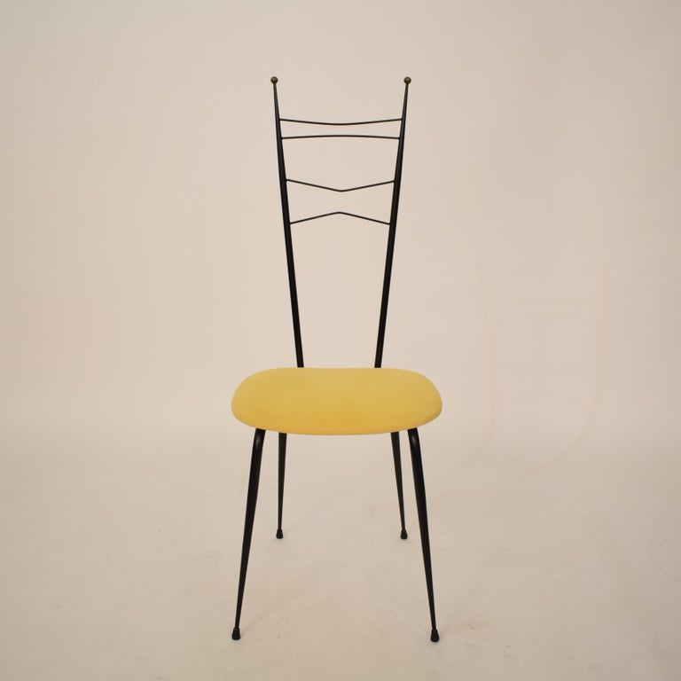 This extraordinary midcentury Italian black and yellow dining room chairs attributed to Ico Parisi and Paolo di Poli is made out of black lacquered metal, brass and yellow fabric.