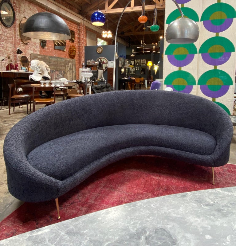 Beautiful from every angle, this large and comfortable midcentury Italian curved sofa has tapered brass legs and luxurious Italian blue wool velvet upholstery sofa is very well made, substantial and comfortable with beautiful lines. Sofa dates 1950s.