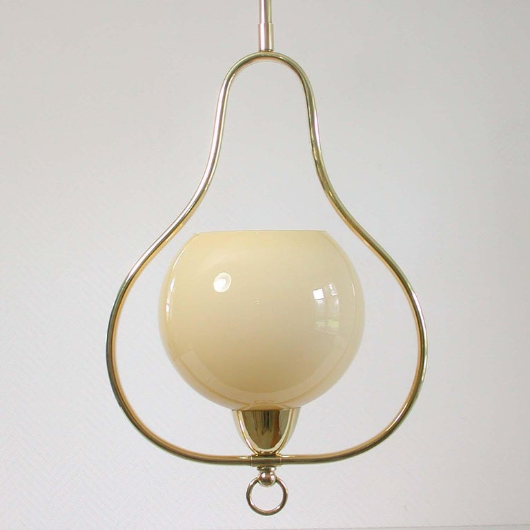 This elegant 1940s-1950s midcentury pendant was designed and manufactured in Italy.  The lamp is made of brass and has got a cream colored opaline lamp shade. The lamp has been rewired. This light can be used in every country of the world. It