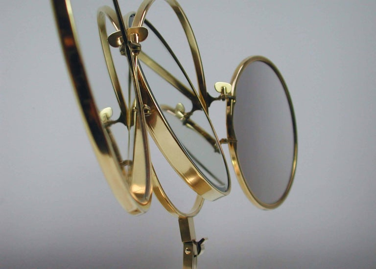 This awesome Mid-Century Modern vanity mirror was made in Italy in the 1950s. It has got a brass base with brass stem and circular mirrors that fold into each other to form a single circle when closed. The centre mirror has two sides (normal and