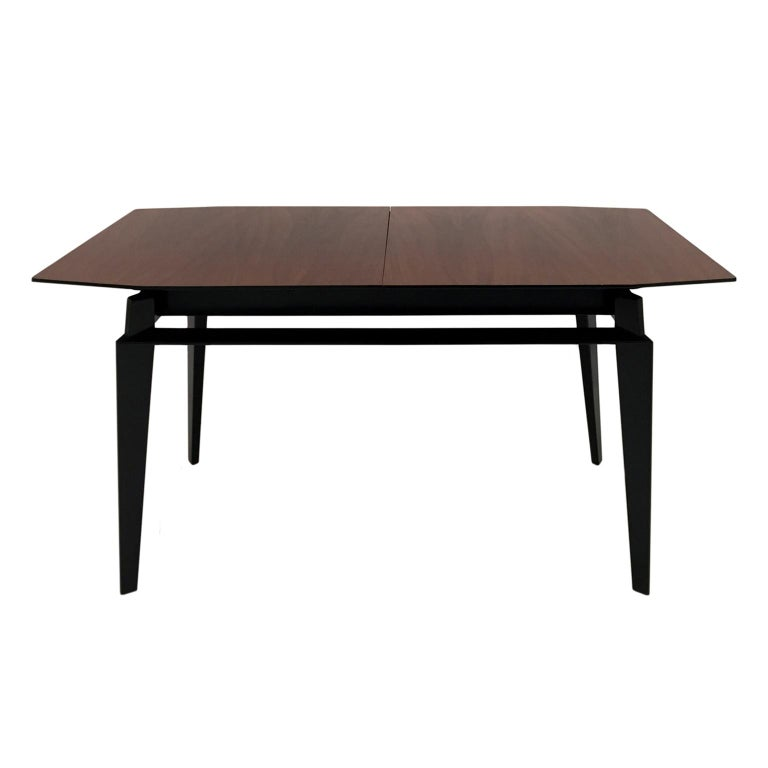 Midcentury extendable dining table by Vittorio Dassi featuring a rosewood veneer tabletop and tapered legs with stretchers. Includes one 12 inch leaf. Italy, 1950s.