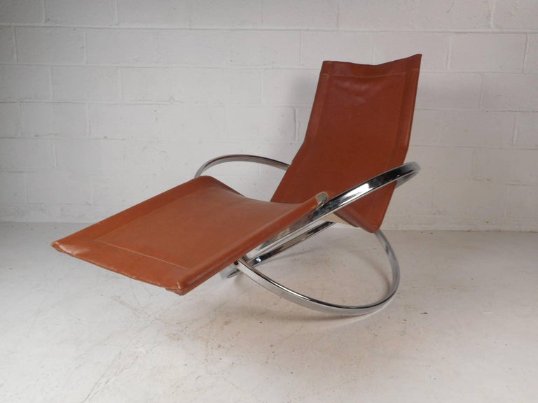 This gorgeous rocking chaise lounge is sure to make a statement in any seating arrangement. Italian design from the 1960s, this chair ensures maximum comfort without sacrificing style. A versatile piece with a hammock style leather seat sitting