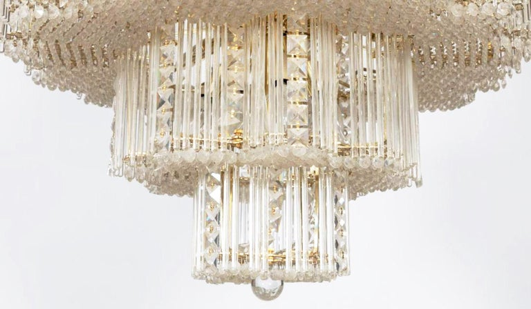 Stunning Sciolari chandelier with his trademark long crystal hanging rods mounted on brass fixtures interspersed with elegant geometric chains of glimmering French cut crystal squares. The removable crystal rods defuse the light of each small bulb