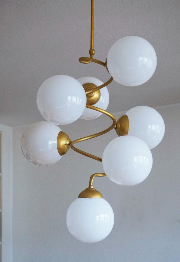 A tall Stilnovo style brass spiral seven-light chandelier with hand blown opaline glass globes, Italy, 1960s. Measures: Height 38